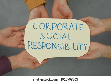 Top view of people holding paper text balloon with phrase Corporate Social Responsibility on grey background, closeup