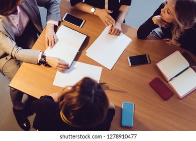Top view of people meeting at the office desk with prepared blank sheets of paper. Seminar, training, education concept
