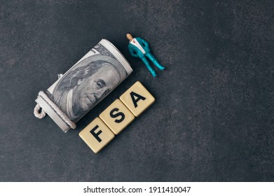 Top view of people miniature, money banknote and scrabble letters with text FSA stands for flexible spending account. - Shutterstock ID 1911410047