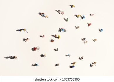 Top view of people (miniature toys) with long shadows keep distance away in public during sunrise or sunset.Social distancing / COVID-19 coronavirus outbreak spreading concept.