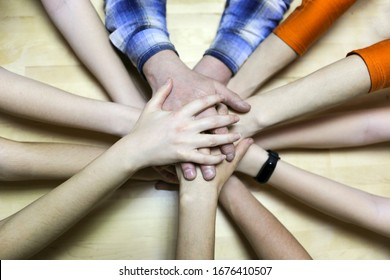 top view of people putting their hands together. Family with stack of hands showing unity and closeness.