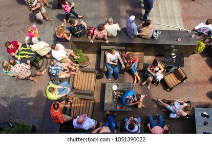 Top view of people sitting around with summer clothing and leis and drinks in an outside sitting area and at tables at P&L District Kansas City Mo May 2 2011