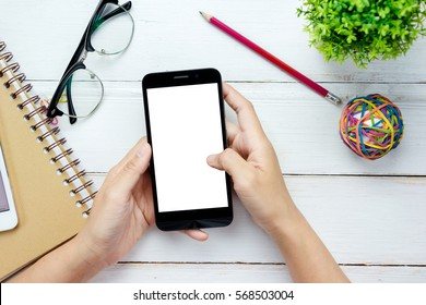 Top view of people are using the mobile phone as a blank screen on the desk.