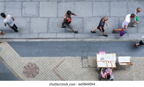 top view of people walk on the pedestrian concrete pavement with the disabled lady on the wheel chair sells the lottery on panel stand.