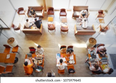 Top view of people working at the co-working space at coffee shop and bakery cafe in the sunny day. Lifestyle of people to work outside the office. Students doing research and homework at wifi cafe.
