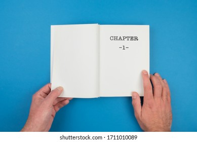 top view of person fiipping open a book with text CHAPTER 1 on first page against blue background