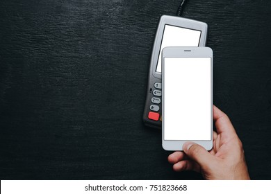 Top view of person using contactless payment with smartphone. Clear white mockup screen template of phone and pos terminal on dark wooden desk with side copy space