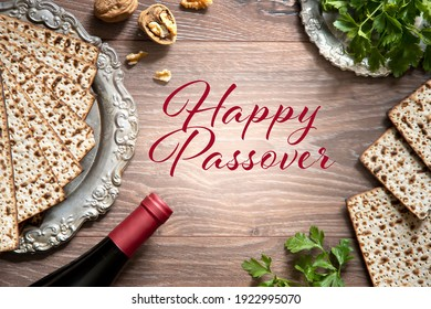 Top view of pesach background. Passover celebration with wine and matzah on the wooden background. With Happy Passover lettering.