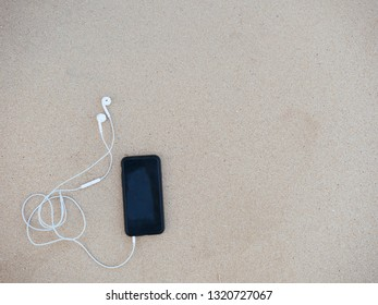 Top view of phone with headphones on sand in a tropical summer beach.