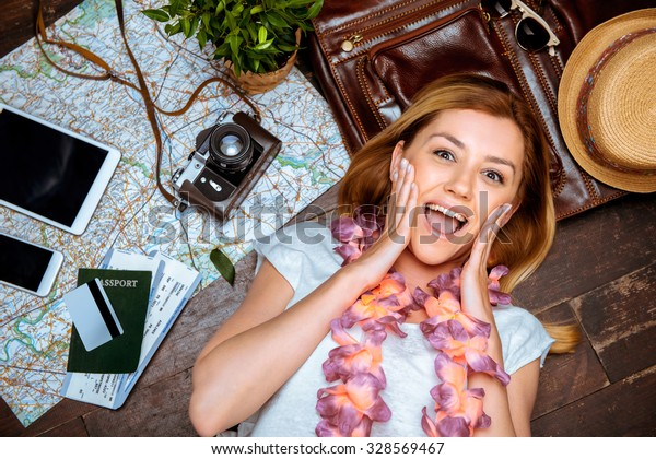 Top view photo of beautiful blonde girl with hawaiian necklace lying on wooden floor. Passport, tickets, electronic devices, hat, vintage camera and map are on floor