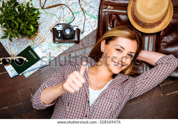 Top view photo of beautiful blonde girl lying on wooden floor. Young woman smiling, showing thumb up and looking at camera. Passport, tickets, vintage camera, hat and map are on floor