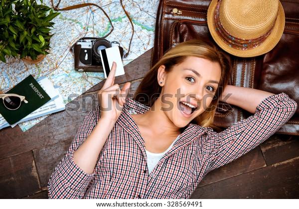 Top-Foto von schönem blonden Mädchen, das auf dem Holzboden liegt. Junge Frau lächelt fröhlich, hält Kreditkarte und sieht Kamera. Reisepass, Eintrittskarten, Vintage-Kamera, Hut und Karte sind auf dem Boden