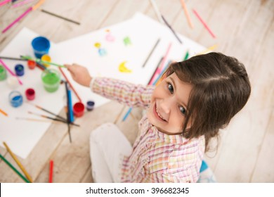 Top view photo of beautiful little girl sitting on wooden floor. Girl looking at camera, smiling and drawing