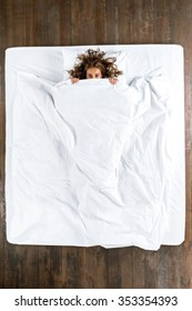 Top view photo of beautiful mixed-race girl lying on big white bed. Young pretty woman wearing pajamas. Girl lying on back, looking at camera and covering herself with blanket
