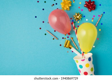 Top view photo of birthday composition blast from paper dotted cup of tinsel sparkles red yellow golden ribbon stars balloons straw pipe and candles on isolated blue background with copyspace
