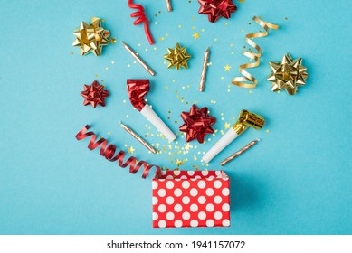 Top view photo of birthday composition blast of tinsel sparkles serpentine red yellow golden ribbon stars pipes and candles on isolated blue background with copyspace