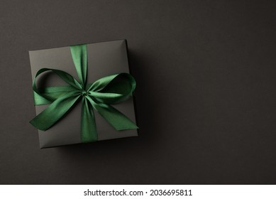 Top view photo of black giftbox with green ribbon bow on isolated black background with empty space
