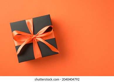 Top view photo of black giftbox with orange satin ribbon bow on isolated orange background with empty space