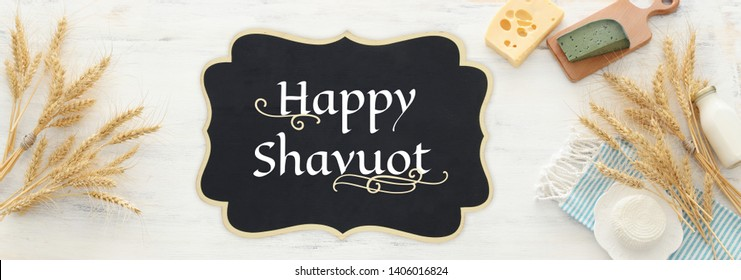 top view photo of dairy products over white wooden background. Symbols of jewish holiday - Shavuot