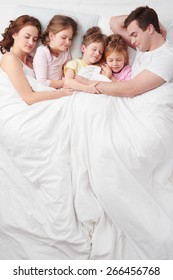 Top view photo of family of five under blanket on white bed. They hugging each other. Children sleeping with their parents