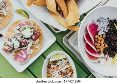 A top view photo of gourmet dishes on a table, with meats salads and chips