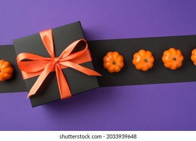 Top view photo of halloween composition black giftbox with orange ribbon bow and small pumpkins in a row on isolated back and violet background with copyspace