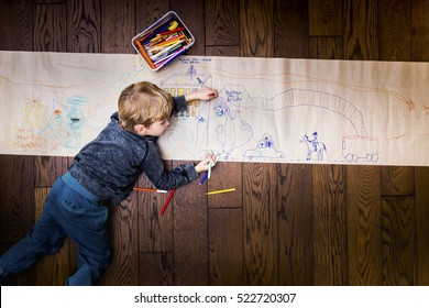 Top view  photo of little boy lying on vintage brown wooden floor and painting.