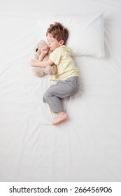 Top view photo of little cute boy sleeping on white bed with teddy bear. Quiet Foetus pose. Concept of sleeping poses