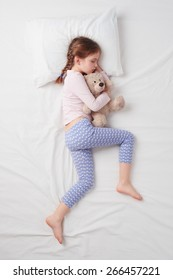 Top view photo of little cute girl sleeping on white bed and hugging teddy bear. Concept of sleeping poses