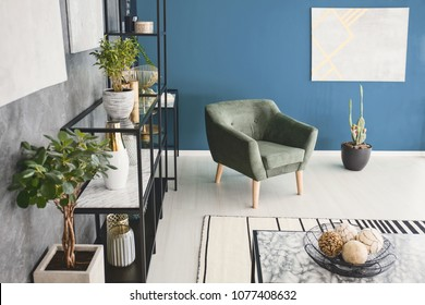 Top view photo of living room interior with green armchair, plants and decor on metal rack and modern painting on the wall