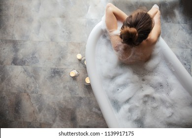 top view photo of modern bathroom with female in foam. quiet and peaceful place for romantic people