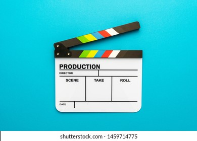 Top view photo of open white clapperboard over turquoise blue background. Flat lay image of blank acrylic movie clapboard. Central composition of movie clapper as filmmaking concept.