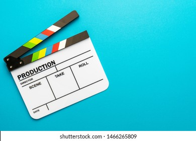 Top view photo of open white clapperboard over turquoise blue background with copy space. Flat lay image of blank acrylic movie clapboard. Left side composition of film clapper as filmmaking concept.