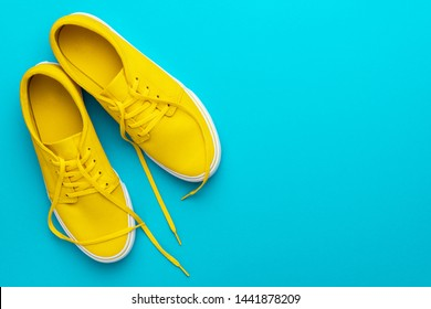 Photo of Top view photo of pair of yellow untied sneakers. Minamalist flat lay image of yellow summer footwear over blue turquoise background with copy space. Left side composition of vivid gumshoes.