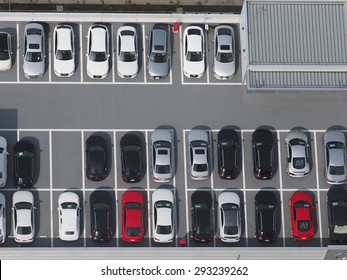 Top view photo of parking lot, taken from 46th floor of skyscraper, with varieties of colored vehicles such as yellow, white, black, grey, silver and blue.