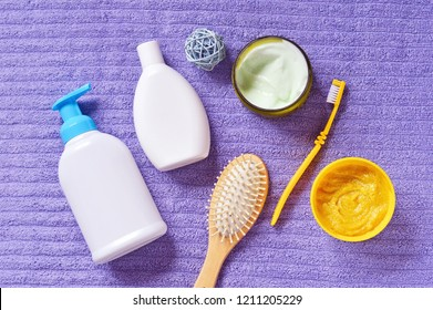 Top view photo personal care items. Flat lay bath products and cosmetics for hair and skin care. Liquid soap bottle, shampoo, body cream jar, toothbrush, yellow scrub on a purple fluffy towel