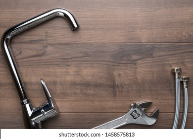 Top view photo of plumbing tools on brown table. Flat lay image of chrome plated handle mixer tap, wrench, flexible hose connectors over wooden background with copy space.