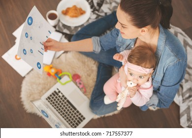 Top view photo of single mom working at home