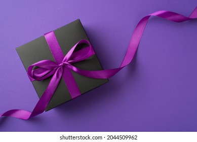 Top view photo of stylish black giftbox with violet satin ribbon bow on isolated violet background with blank space