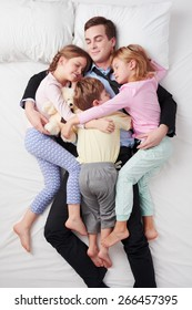 Top view photo of tired businessman wearing suit, and his three children. Father's arms are over daughters and son. They sleeping on white bed and hugging each other