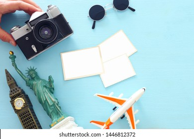 Top view photo of traveling concept with accessories, blank photo frames for mockup and world symbols over blue background