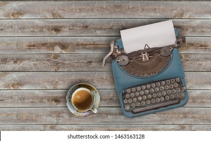 top view photo of vintage typewriter with blank page next to cup of coffee, on wooden table.