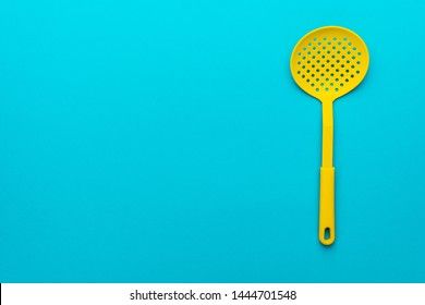 Top view photo of vivid plastic kitchen utensil. Minimalistic flat lay image of yellow skimmer spatula over turquoise blue background with copy space and right side position.