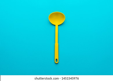 Top view photo of vivid plastic kitchen utensil. Minimalist flat lay image of yellow ladle over turquoise blue background with copy space. Central composition of dipper on blue table.