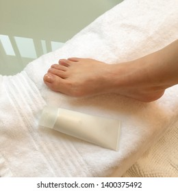 Top view photo of woman feet on a white towel after bath beside with a skin lotion