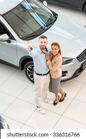Top view photo of young couple with car key after successful deal in auto show. Concept for car rental