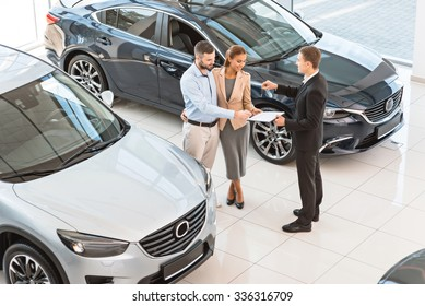 Top view photo of young male consultant and buyers signing contract for new car in auto show. Concept for car rental