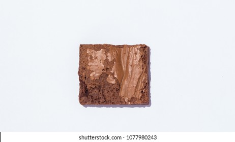 Top view photograph of a perfect square fresh baked chocolate brownie over a clean white background