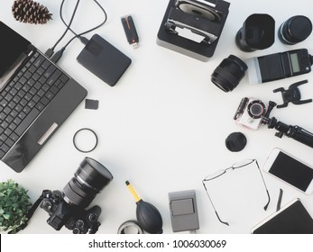 top view of photographer concept with digital camera, battery charger camera, memory card storage box, external harddisk, flash, notebook and camera accessory on white background with copy space.