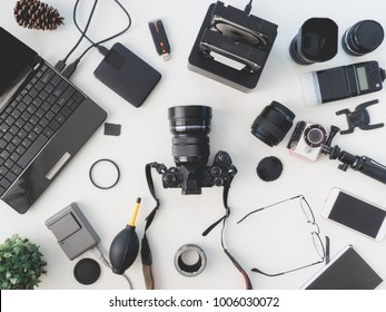 top view of photographer concept with digital camera, battery charger camera, memory card storage box, external harddisk, flash, computer laptop, notebook and camera accessory on white background.